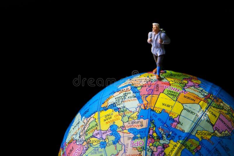 在地球世界地图的微小的玩具旅行 免版税图库摄影
