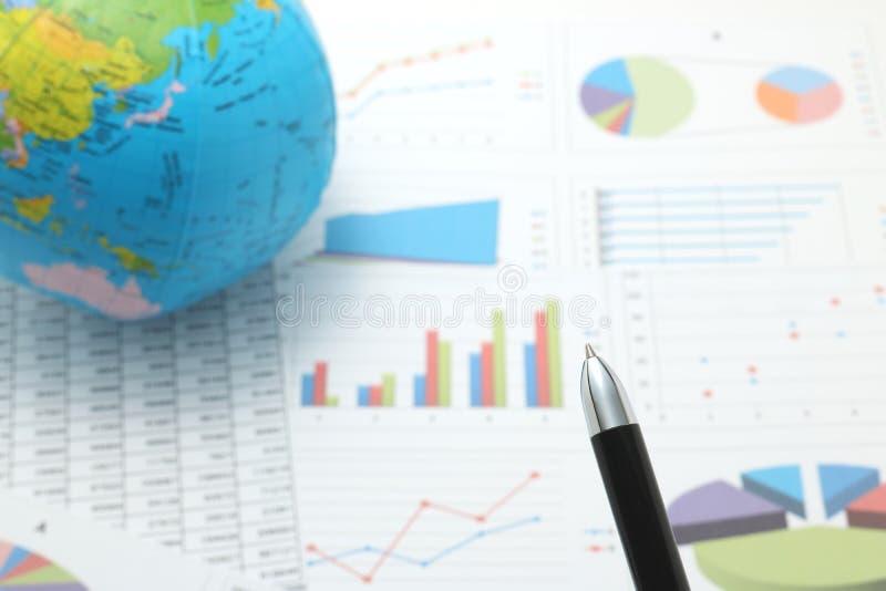 在地球和纸前面的笔与数字和图 免版税库存照片