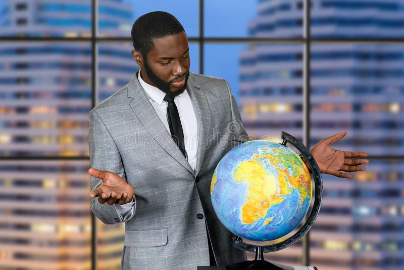 在地球旁边的困惑的非洲的商人 免版税库存照片
