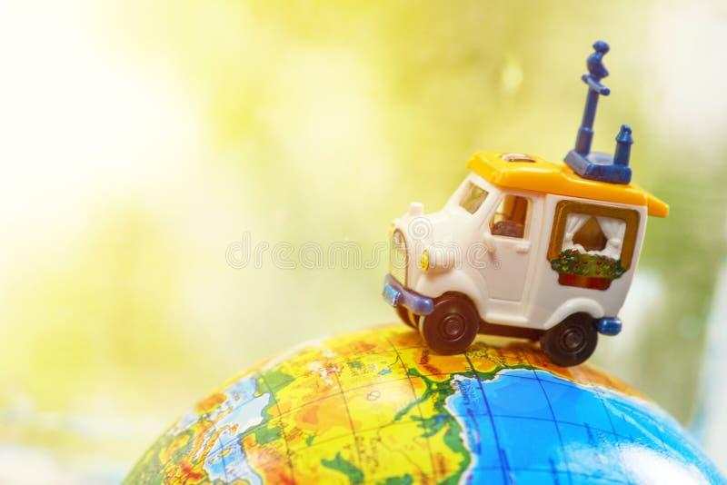 在地球的一辆汽车在绿色背景 在地球的微型汽车玩具 汽车城市概念都伯林映射小的旅行 库存照片