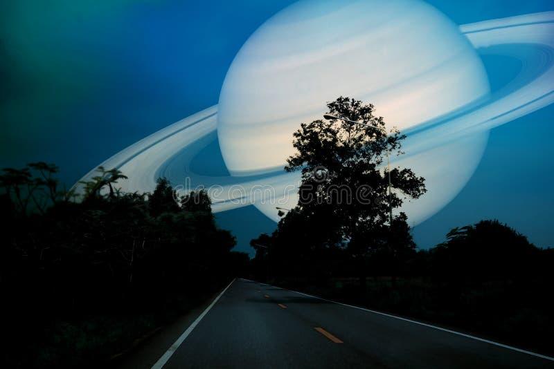 在地球附近的土星在乡下公路的夜空 库存图片