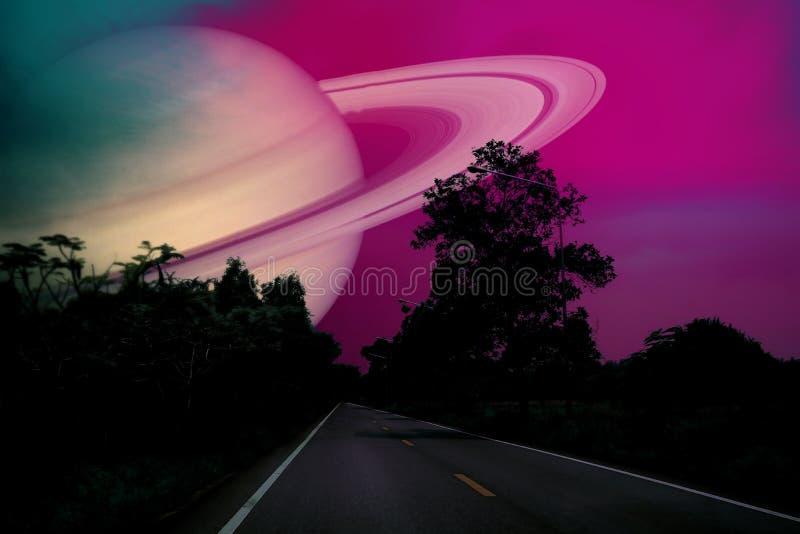 在地球附近的土星在乡下公路的夜空 免版税库存照片