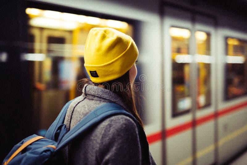 在地铁车站的年轻女人等待,当火车arrrives时 运输和旅行概念 免版税库存图片