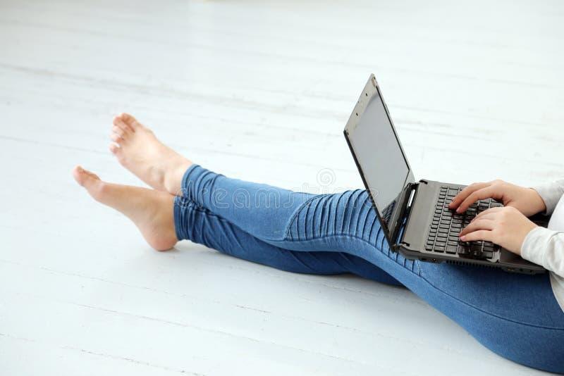 在地面上的女孩与膝上型计算机 库存照片