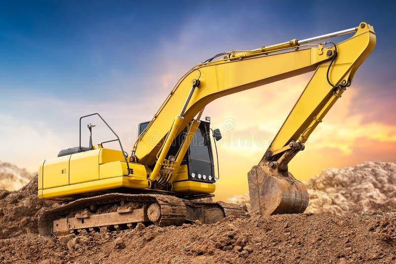 在地面上的挖掘机反向铲在工地工作在日落背景中 免版税库存照片