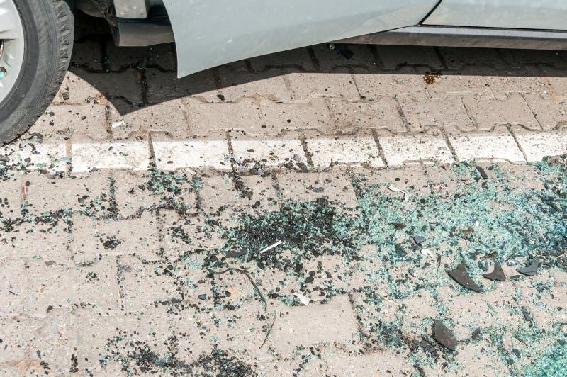 在地面上的残破和被打碎的窗口或挡风玻璃玻璃从损坏的汽车 免版税库存图片