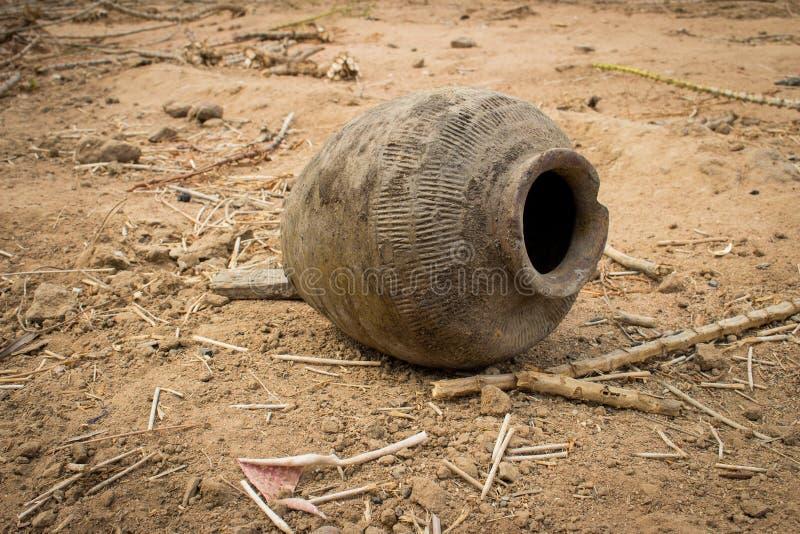 在地面上的老使用的和打破的泥罐 库存照片