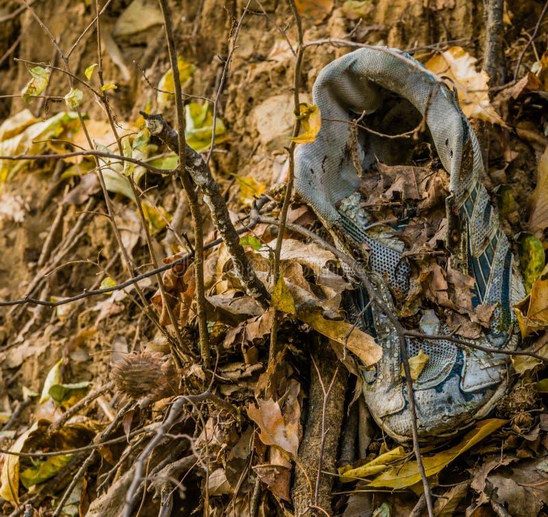 在地面上的老被放弃的体育鞋子 免版税库存照片