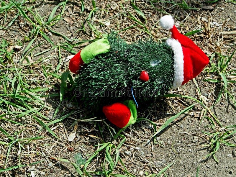 在地面上的被放弃的圣诞树玩具 图库摄影
