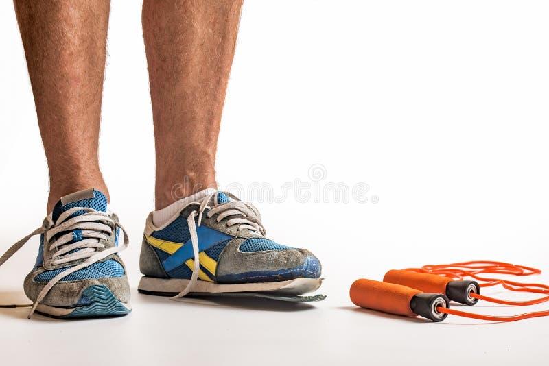 在地面上的身分佩带被用完的对教练员的人和跳绳-健康健身和训练概念图象 免版税库存照片