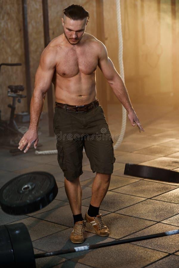 在地面的年轻体育人导弹有效载荷重量板材在健身房 库存图片