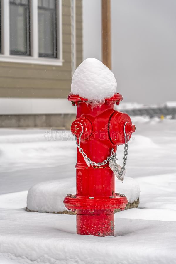 在地面的红火消防栓与雪毯子  免版税库存图片