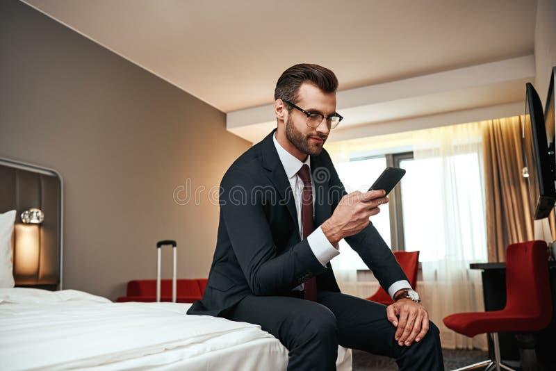 在坐与智能手机的西装的商人在床在酒店房间 免版税库存照片