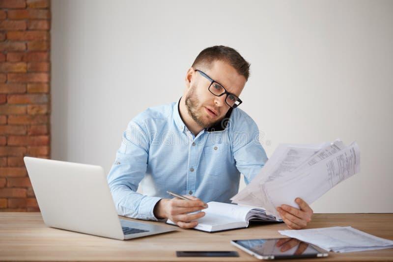 在坐在一个舒适的轻的办公室的玻璃和衬衣的繁忙的被集中的未剃须的商人,通过看 库存图片