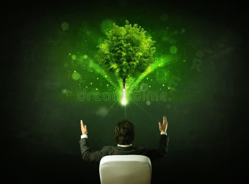 在坐在一棵发光的树前面的椅子的商人 库存照片