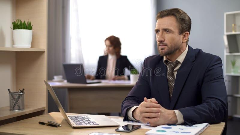 在坐在书桌和考虑收入,工作场所的西装的男性 免版税库存图片