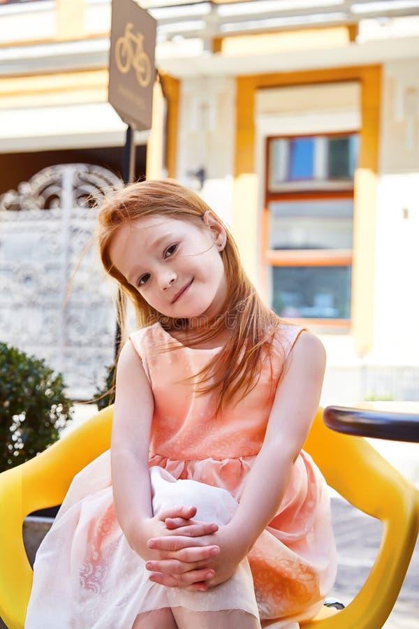 在坐在咖啡馆的时尚礼服的美好的小女孩穿戴 库存照片