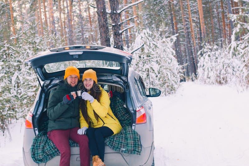 在坐在有一根开放树干的一辆汽车的爱的夫妇 免版税库存图片