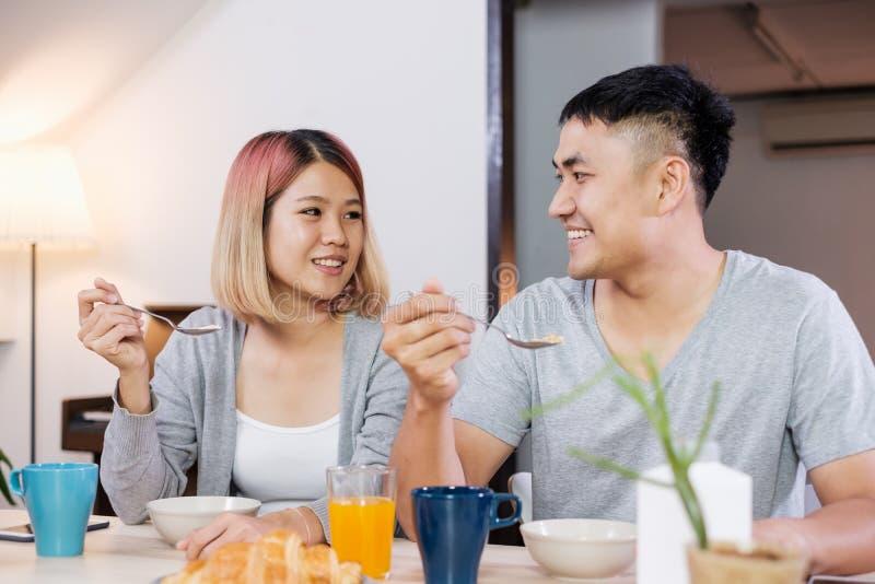 在坐在桌上的睡衣的愉快的亚洲夫妇在厨房里在hom 免版税库存图片