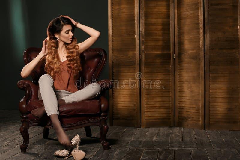 在坐在棕色皮革扶手椅子的时装的时装模特儿摆在演播室 免版税库存图片