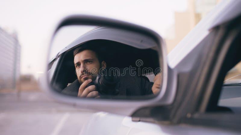 在坐在汽车里面和拍摄与dslr照相机的年轻私家侦探人旁边镜子的反射  免版税库存照片