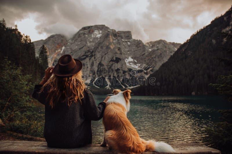 在坐在湖拉戈di Braies附近的孩子和狗之间的友谊 免版税库存图片