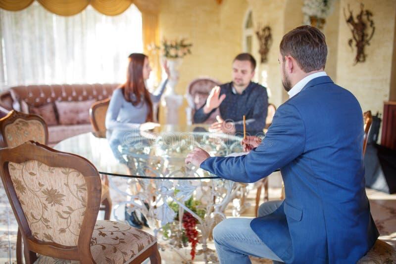 在坐在玻璃桌上的年轻夫妇争吵的心理学家,篡改坐在椅子听 图库摄影