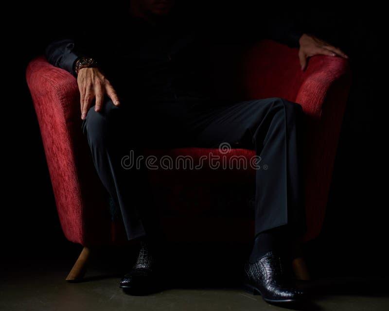 在坐在红色椅子,黑背景,没有面孔可看见,演播室射击的一套黑衣服的男性商人 库存图片