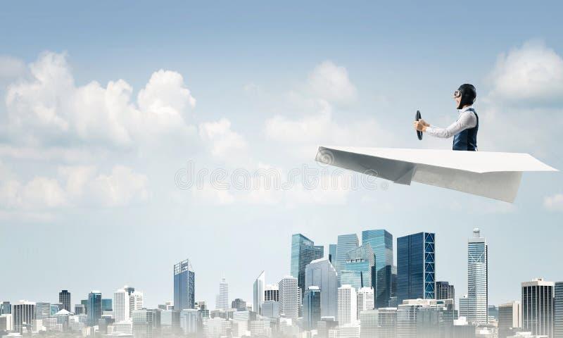 在坐在纸飞机的飞行员帽子的商人 库存照片