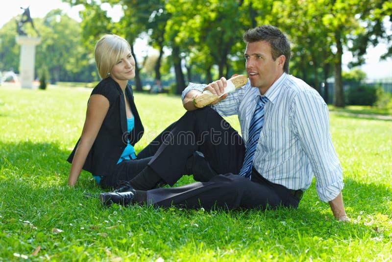 在坐在草的午休的商人 图库摄影