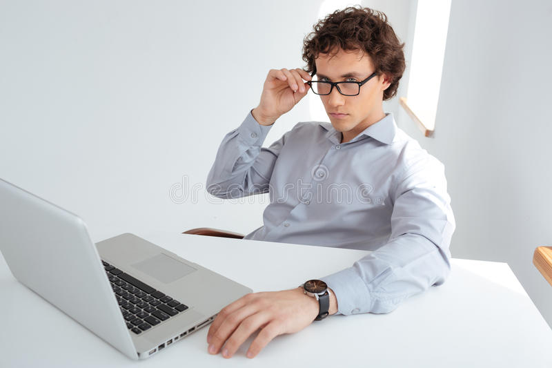 在坐在他的工作场所的玻璃的商人 图库摄影