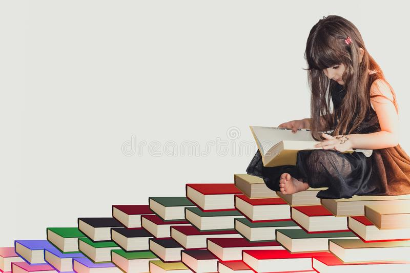 在坐堆书读书和学会知识和信息的一件黑礼服的一个明智的矮小的逗人喜爱的女孩孩子 图库摄影