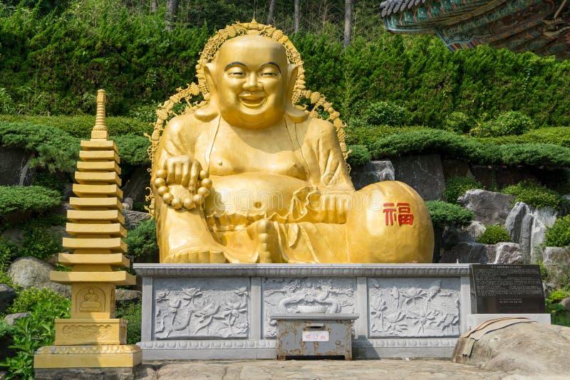 在坐姿雕象的金黄微笑的肥胖菩萨图象在Ha 免版税库存照片