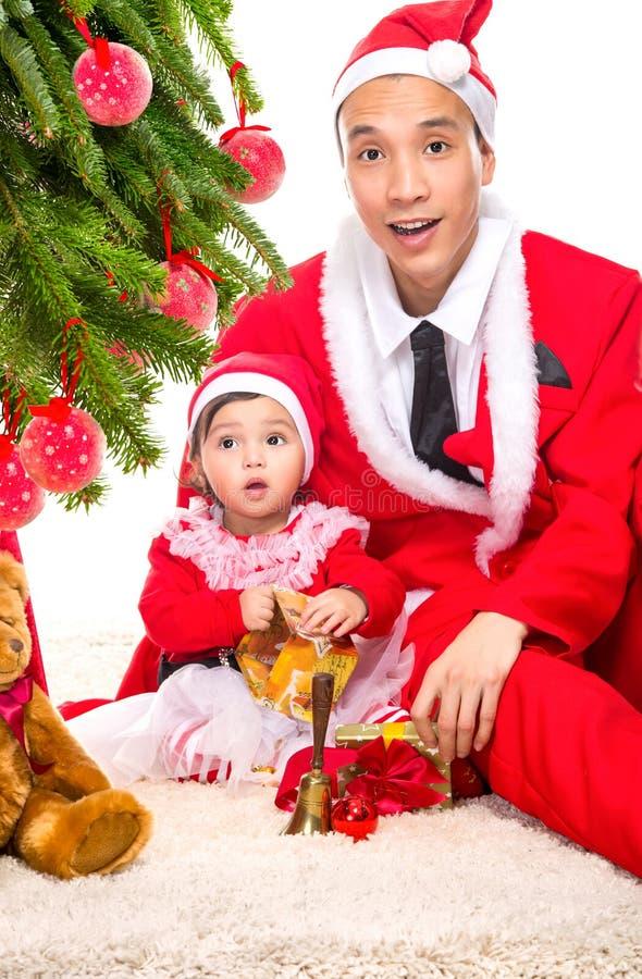 在坐的圣诞前夕的愉快的家庭在家近 库存照片