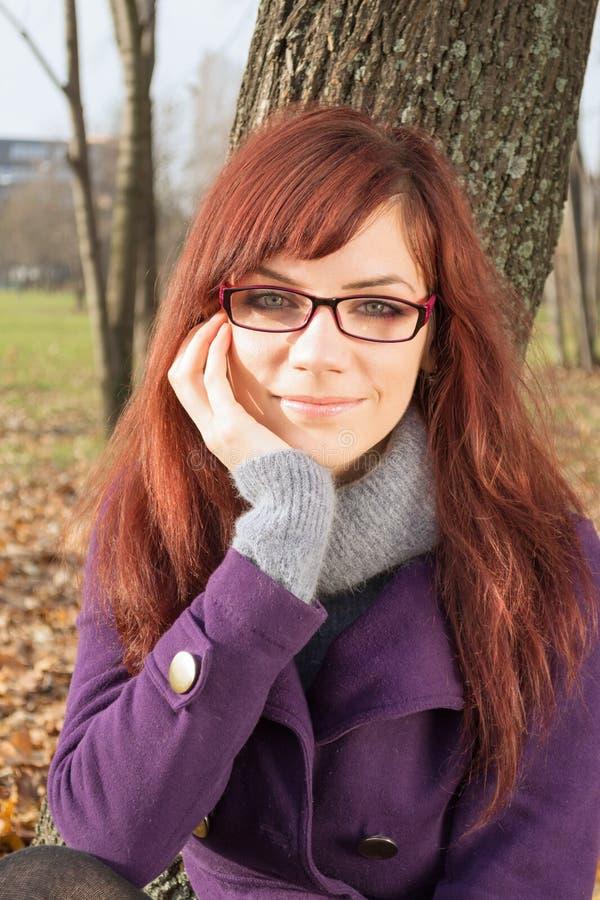 在坐的结构树妇女年轻人附近 图库摄影