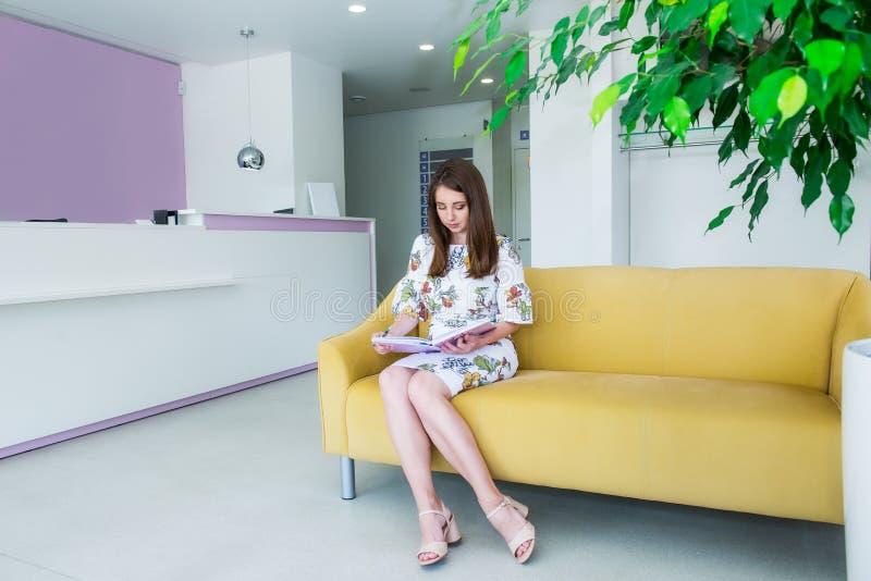 在坐黄色沙发在企业大厅里和写在笔记本的微笑的年轻女商人充分的成长画象, 免版税库存照片
