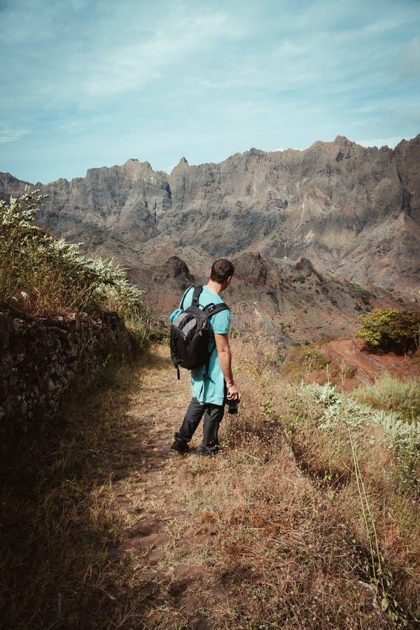 在坚固性山脉前面的远足者赞赏的贫瘠自然风景 迁徙的足迹在从Corda的一个晴天 免版税库存照片