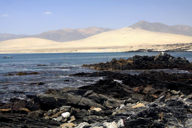 在坚固性石头和偏僻的盐水湖贫瘠干燥小山的-阿塔卡马沙漠太平洋海岸的巴伊亚Inglesa的看法  免版税库存照片