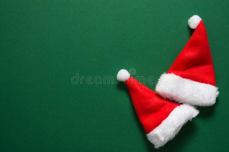 在坚实深绿背景的两个圣诞老人项目帽子 圣诞节新年假日贺卡海报横幅占位符 免版税图库摄影