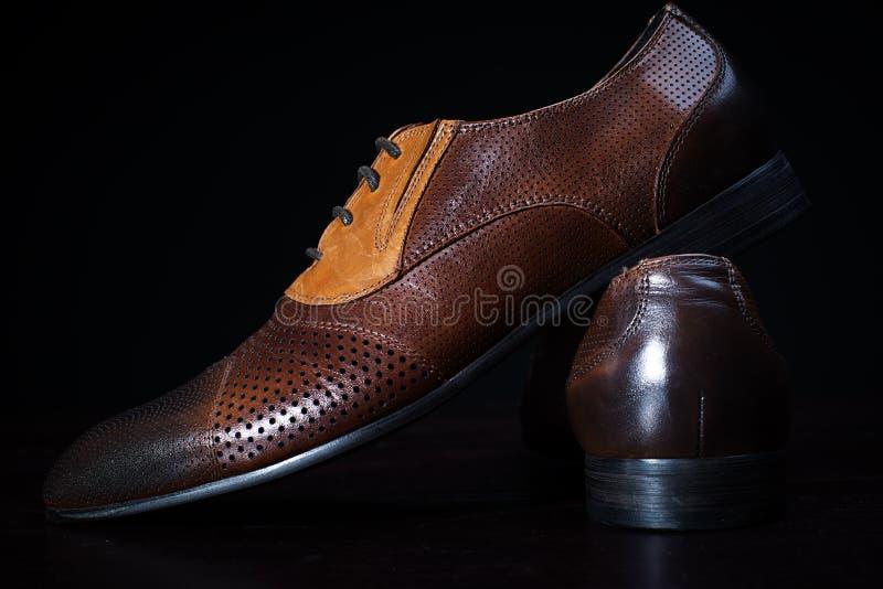 在坚实黑背景的男性鞋子 免版税库存照片