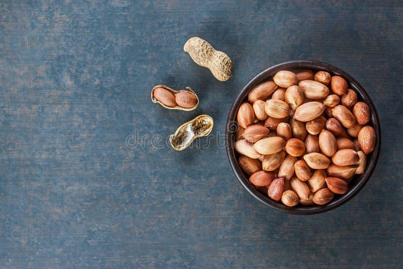 在坚果壳的花生在木背景的棕色碗 花生的构成 免版税库存照片