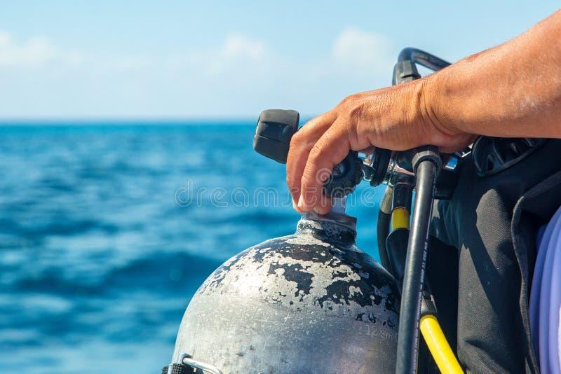 在坦克特写镜头的轻潜水员手 免版税图库摄影