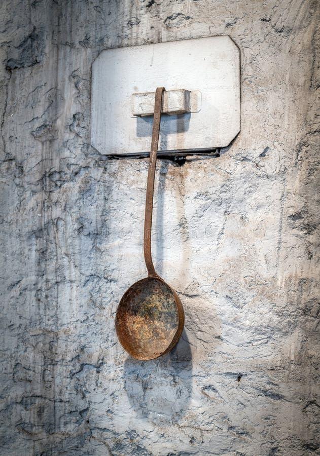 在垂悬在墙壁上的商店金属化浸洗匙子的炉渣 库存图片