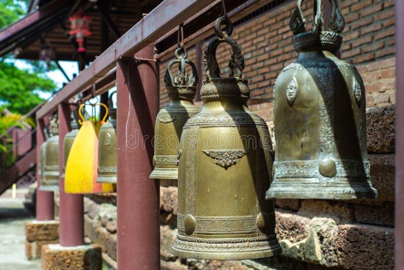 在垂悬在铁棍的黄铜响铃的选择聚焦在佛教寺庙 免版税库存图片