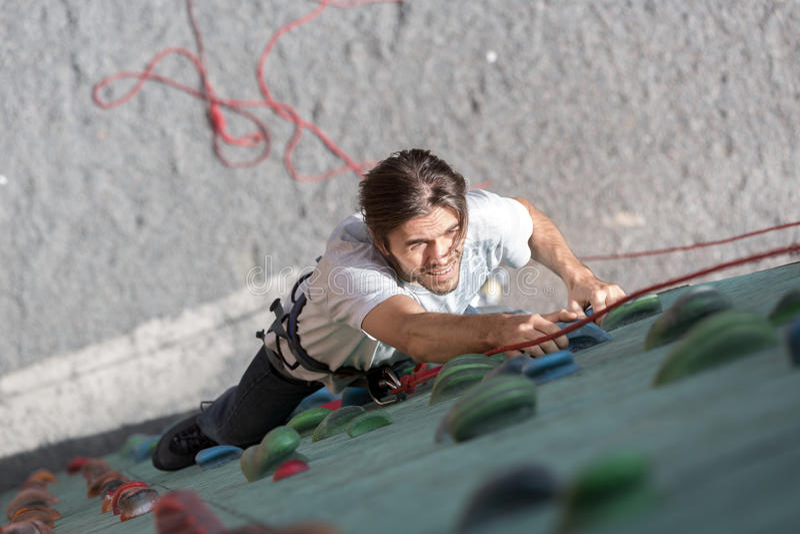 在垂直的墙壁上的成熟男性攀岩运动员 免版税库存照片