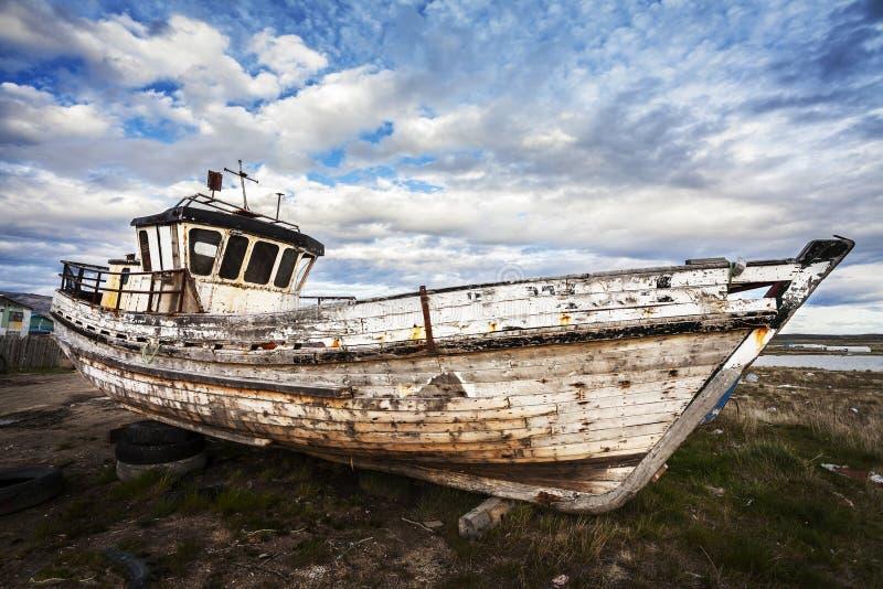 在垃圾场的老小船 库存图片