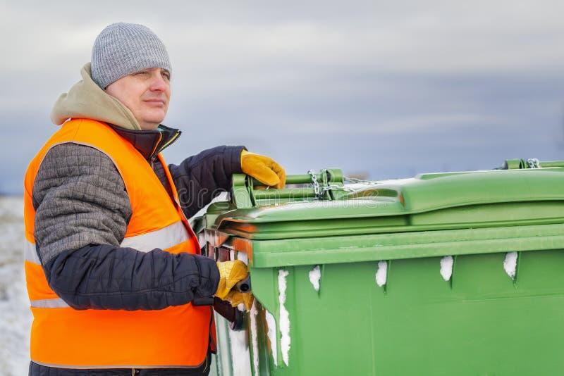 在垃圾容器附近的工作者在冬天 免版税库存图片