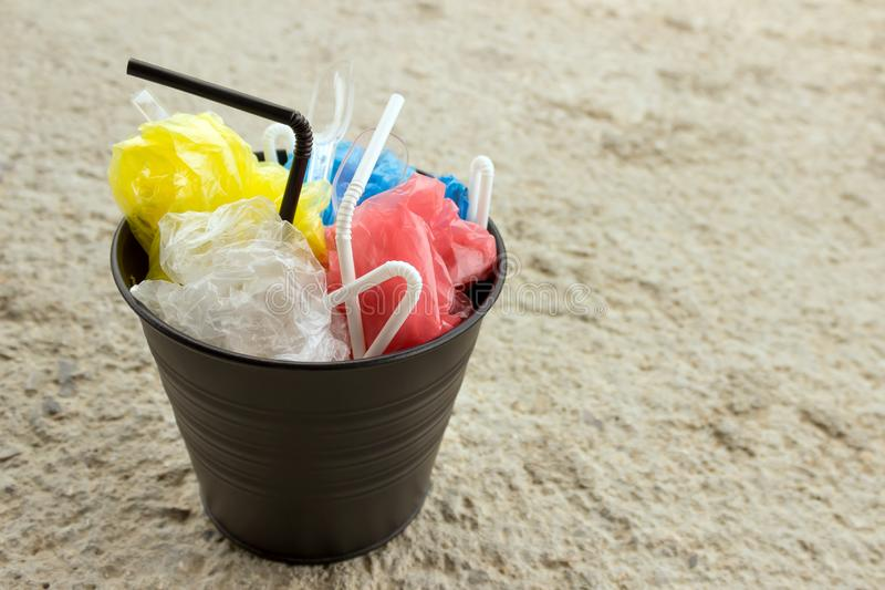 在垃圾桶是垃圾由塑料制成:袋子,一次性匙子,鸡尾酒的管 免版税库存照片