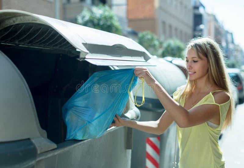 在垃圾桶附近的妇女 免版税库存照片