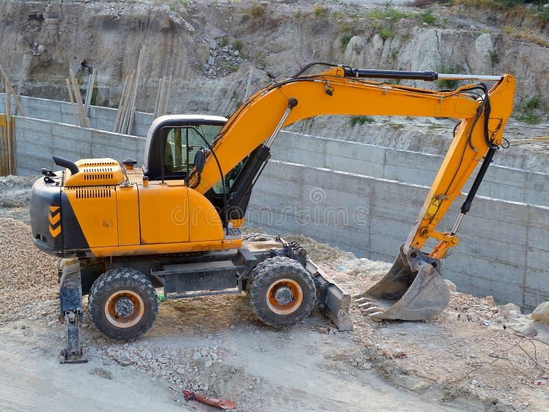 在垄沟的黄色挖掘机在道路施工工作的站点 免版税库存照片